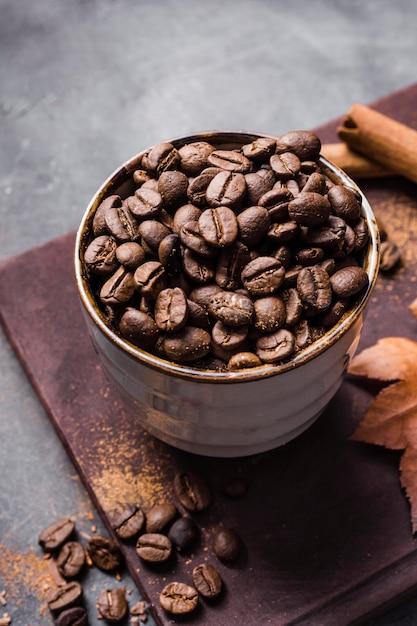 Кофейные зерна высокого угла в чашке на разделочной доске с корицей Premium Фотографии