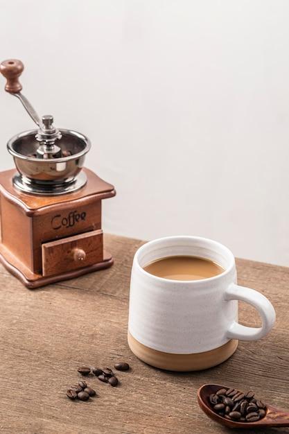 Elevato angolo di macinino da caffè con tazza e chicchi di caffè Foto Gratuite