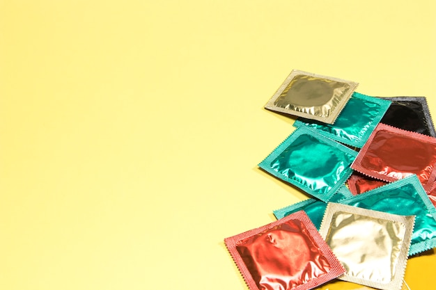 High angle colourful condoms on yellow background Free Photo