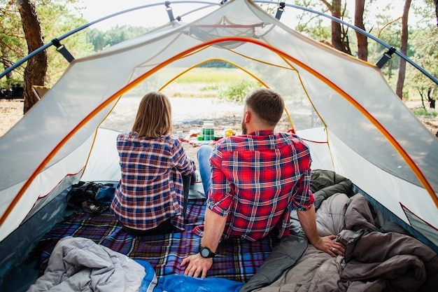High angle couple enjoying nature view from tent Free Photo