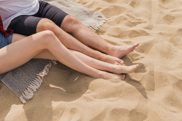 High angle of couple with feet in sand Free Photo