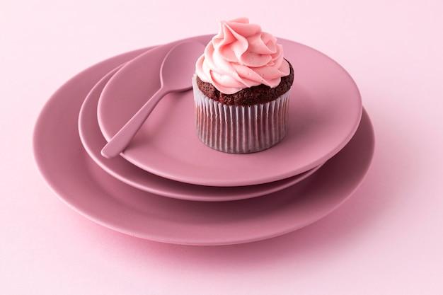 皿の上の高角度のカップケーキとスプーン 無料写真
