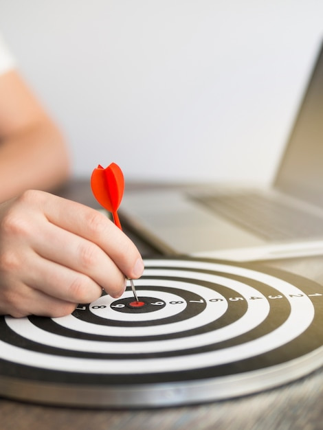 High angle of dart held by hand with dart board Premium Photo