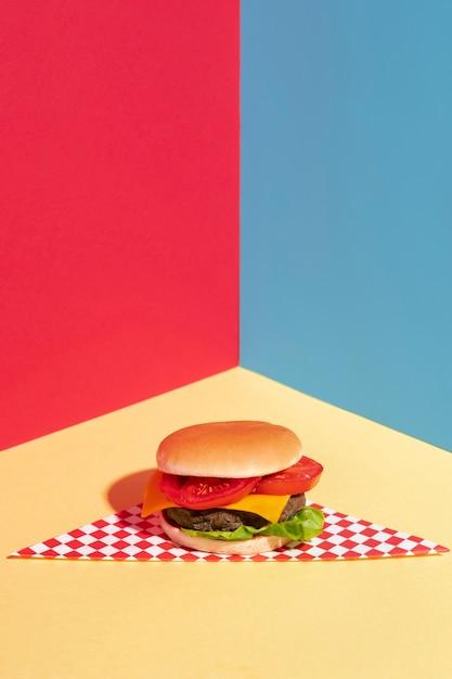 Высокий угол украшения с вкусным чизбургером на желтом столе Бесплатные Фотографии