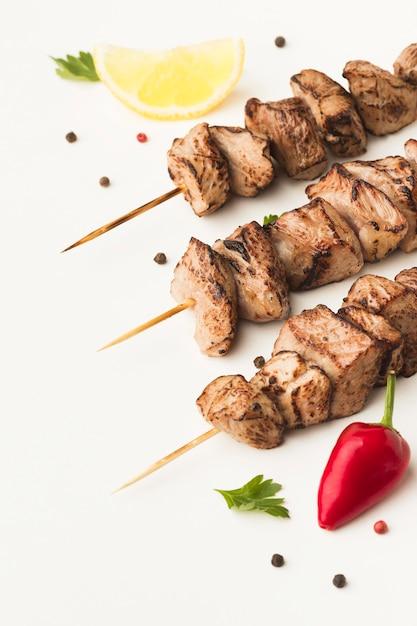 Angolo alto di delizioso kebab con peperoncino e limone Foto Gratuite