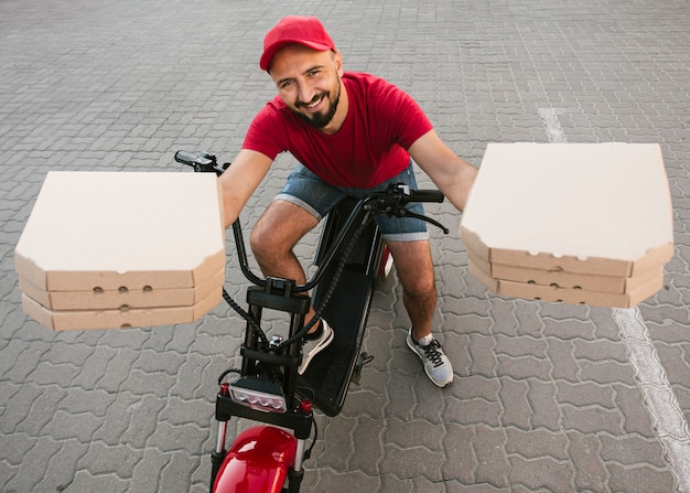 High angle delivery guy holding pizza boxes Free Photo