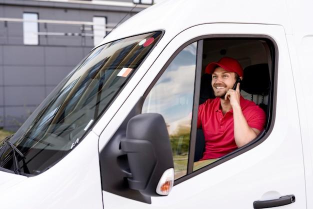 Uomo di servizio di consegna dell'angolo alto che parla sopra il telefono Foto Gratuite