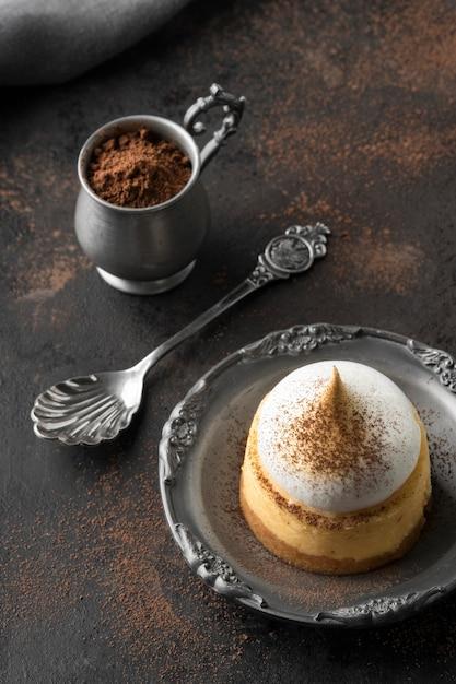 Alto angolo di dessert sulla piastra con cacao in polvere Foto Gratuite