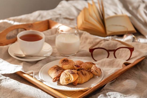 Alto angolo di dessert sul vassoio con bicchieri e tè Foto Gratuite