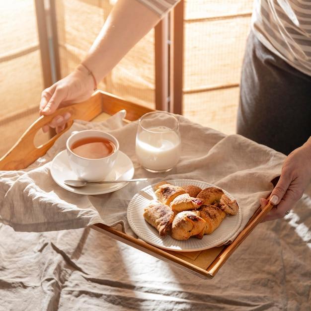 Alto angolo di dessert sul vassoio con latte e tè Foto Gratuite