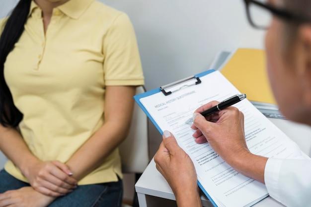 Medico di alto angolo che consulta un paziente nel suo ufficio Foto Gratuite