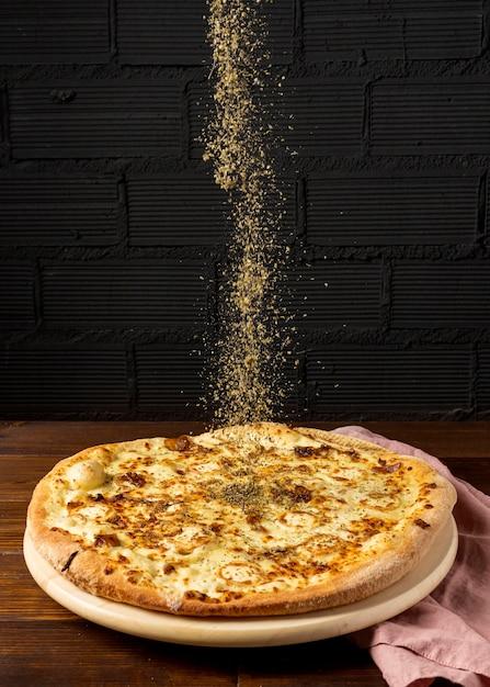Erbe secche ad alto angolo cosparse sulla pizza Foto Gratuite
