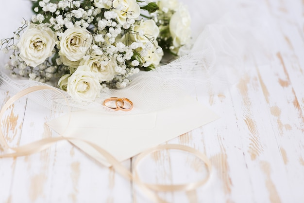 High angle engagement rings beside flowers Free Photo