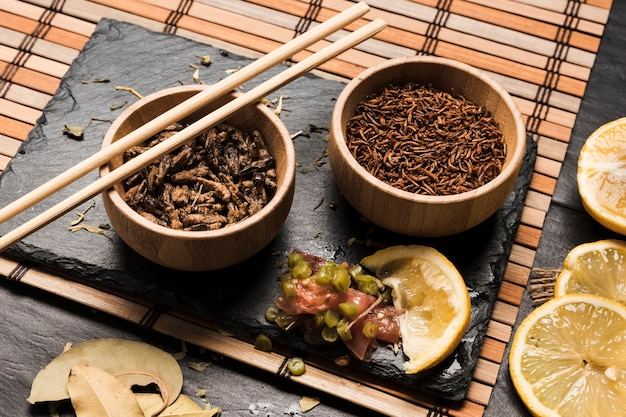 High angle of exotic food in bowls with sticks Free Photo