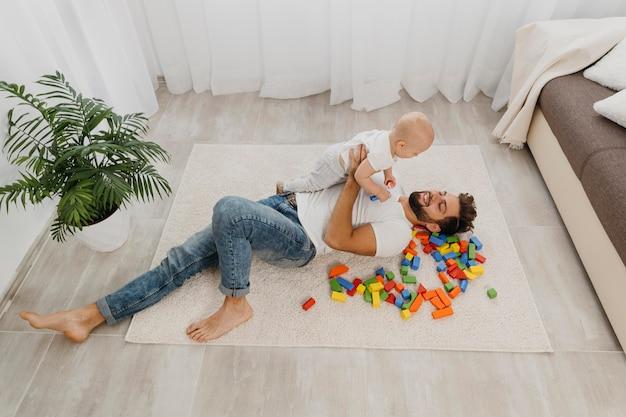 Alto angolo del padre che gioca sul pavimento a casa con il bambino Foto Gratuite