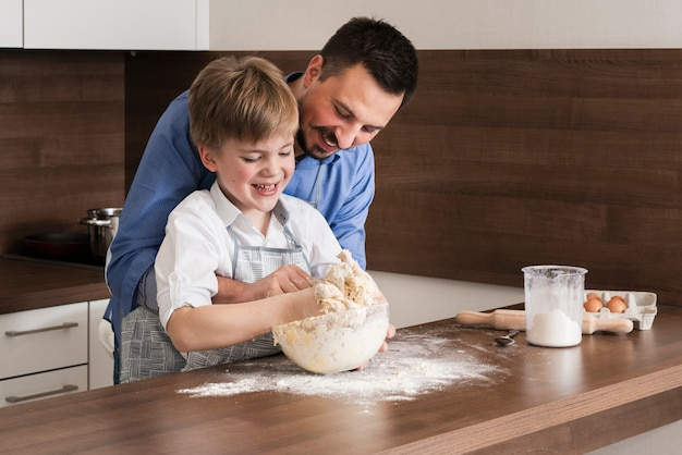 High angle father and son making together dough Free Photo