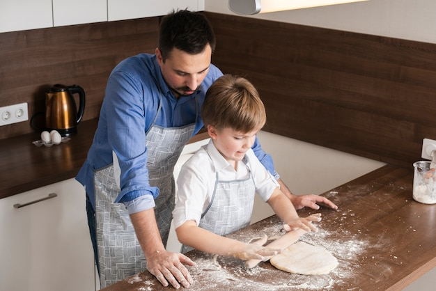 High angle father teaching son to roll dough Free Photo