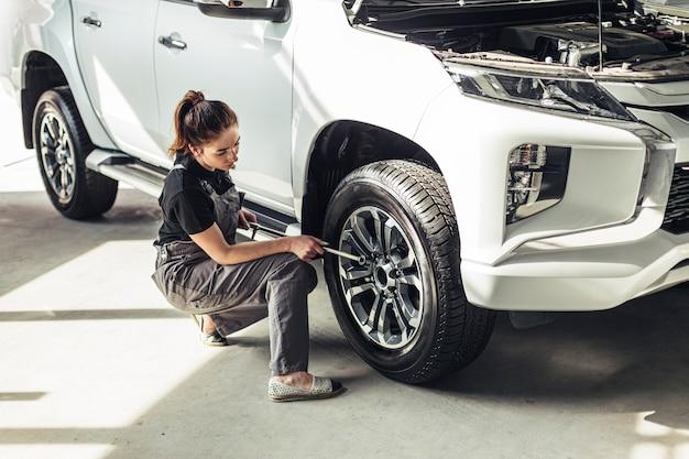 High angle female mechanic taking out wheel Free Photo