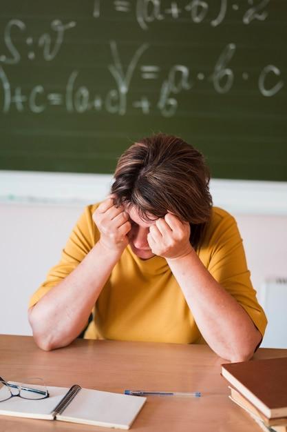 Insegnante femminile di alto angolo allo scrittorio stanco Foto Gratuite