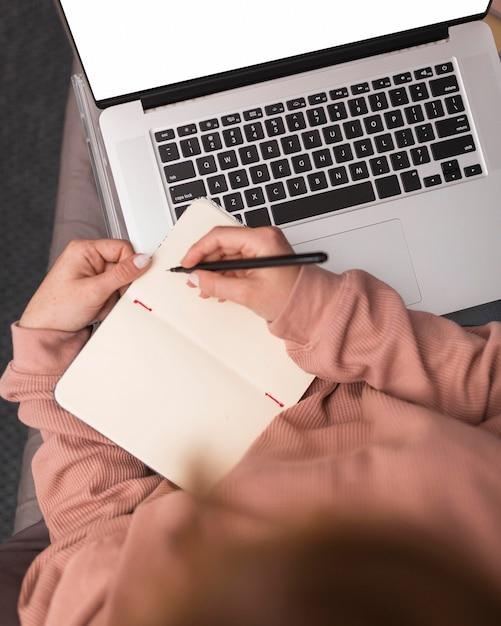 Alto angolo di insegnante femminile a casa che scrive in agenda durante la lezione online Foto Gratuite