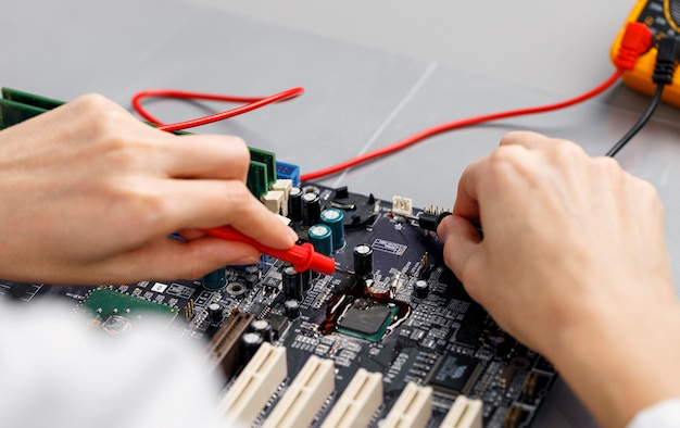 High angle of female technician repairing computer motherboard Free Photo