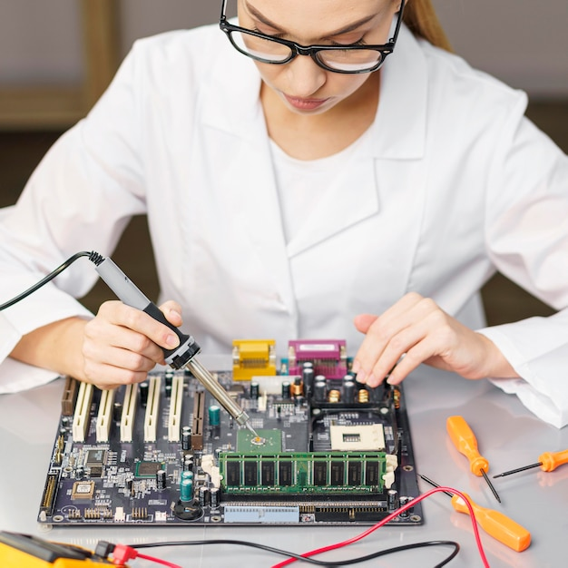High angle of female technician with electronics and soldering iron Free Photo