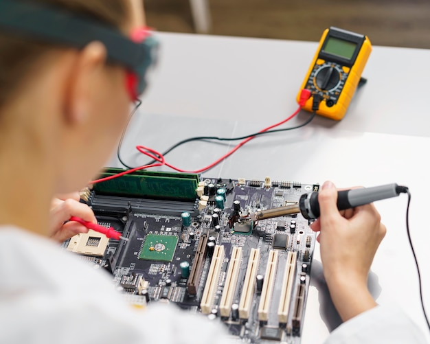High angle of female technician with soldering iron and electronics motherboard Free Photo