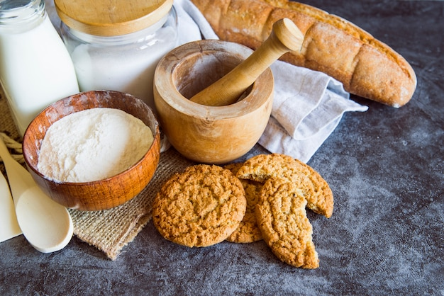 High angle of flour with cookies and bread Free Photo