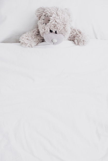 High angle fluffy teddy bear in bed Free Photo