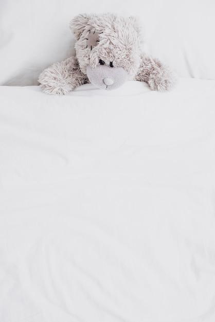 ベッドの中で高角度のふわふわテディベア Premium写真