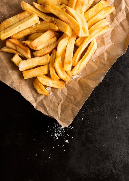 Alto angolo di patatine fritte su carta con sale Foto Gratuite