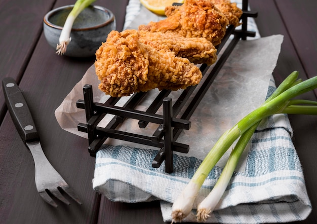 Ali di pollo fritte ad alto angolo sul vassoio con cipolle verdi e forchetta Foto Gratuite