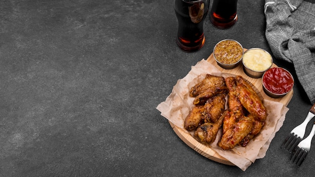 High angle of fried chicken wings with variety of sauces and fizzy drinks Free Photo