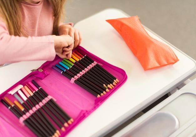 Девушка под высоким углом берет карандаш из пенала Бесплатные Фотографии