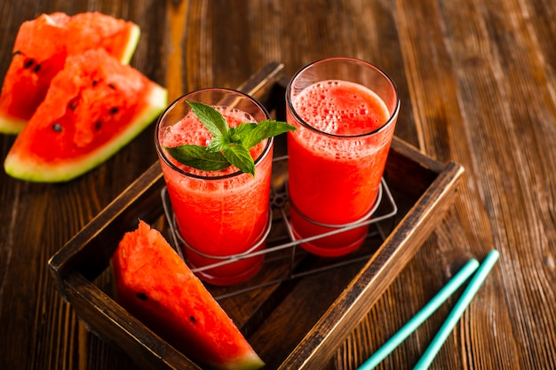 High angle glasses in cup holder with watermelon juice Free Photo