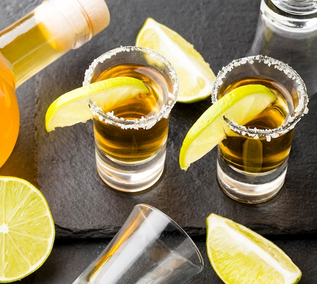 Colpi di tequila d'oro ad alto angolo e lime con sale e bottiglia Foto Gratuite