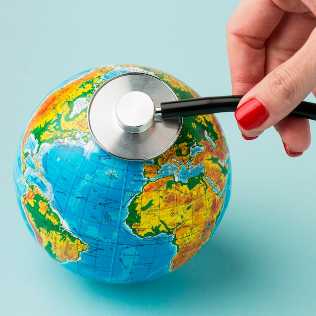 High angle of hand consulting earth with stethoscope Free Photo