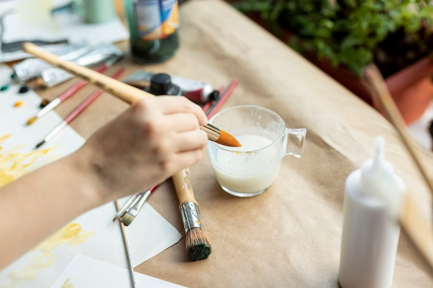 High angle hand holding painting brush Free Photo