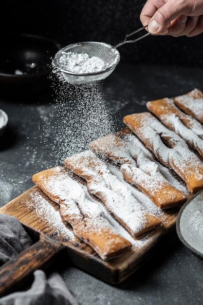 Elevato angolo di setacciatura a mano di zucchero a velo sui dessert Foto Gratuite