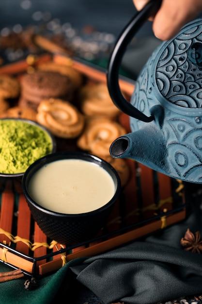 Высокий угол рука с чайником наливая напиток Бесплатные Фотографии