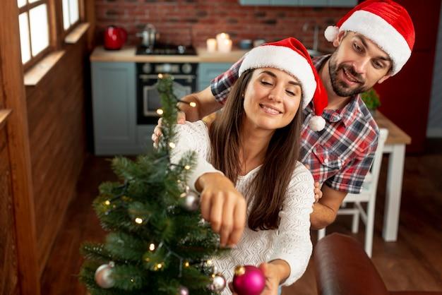 High angle happy couple decorating the christmas tree Free Photo