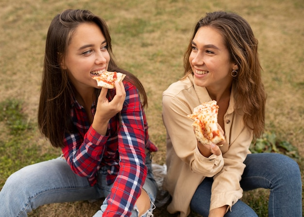 High angle happy girls eating pizza Free Photo