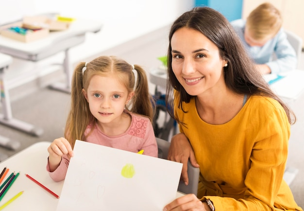 Ребенок под высоким углом показывает свой рисунок со своим учителем Бесплатные Фотографии