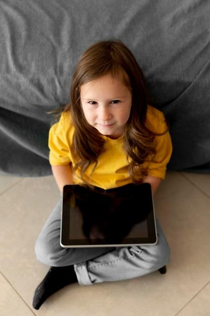 Alto angolo della bambina facendo uso della compressa Foto Gratuite