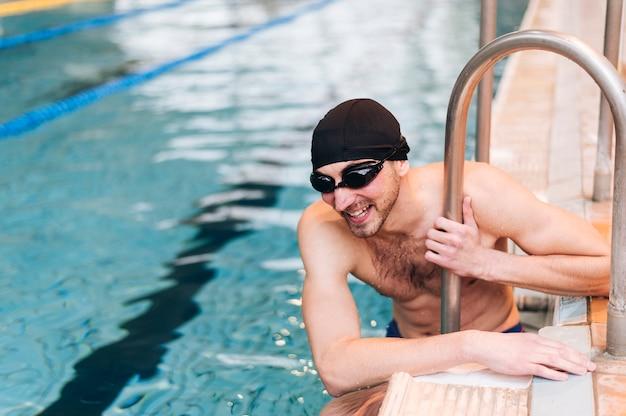 Nuotatore maschio dell'angolo alto sulla pausa Foto Gratuite
