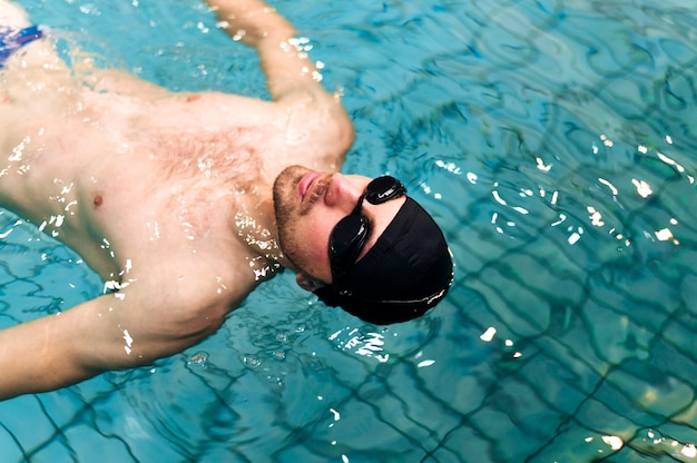 High angle male swimming on back Free Photo