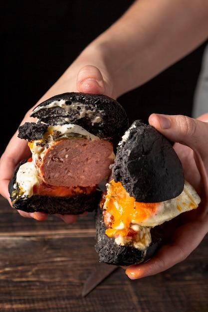 Hamburger della holding dell'uomo di alto angolo tagliato a metà Foto Gratuite