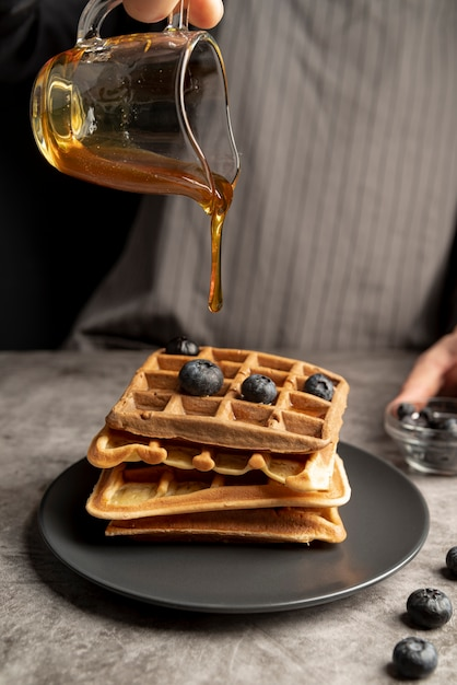 High angle of man pouring syrup of stack of waffles Free Photo