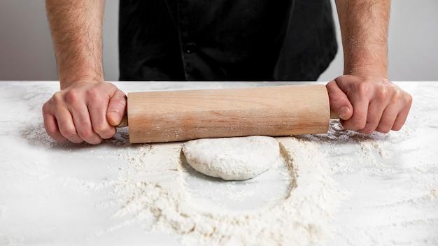 Impasto della pizza di rotolamento dell'uomo di alto angolo Foto Gratuite
