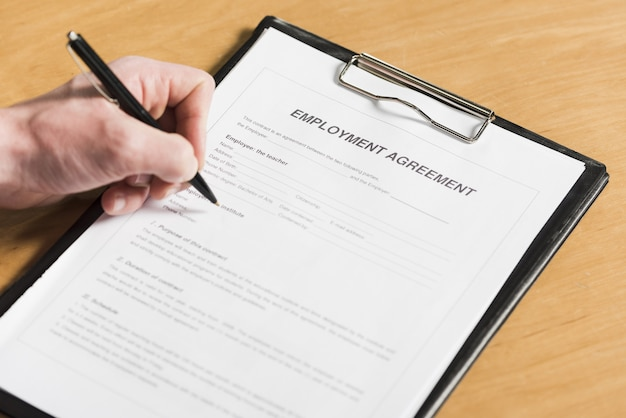 High angle of man signing contract for new job Free Photo